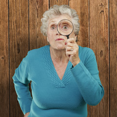portrait of senior woman looking through a magnifying glass agai