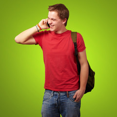 portrait of young man talking on mobile over green background