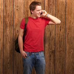 portrait of young man talking on mobile against a wooden wall
