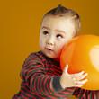portrait of funny kid holding a big orange balloon over orange b