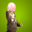 portrait of funny kid trying to hold a pink balloon over green b