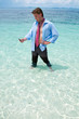 Funny business man calling by cell phone on the beach