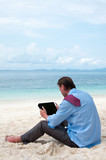 Business man working on the beach with tablet computer - Fine Art prints