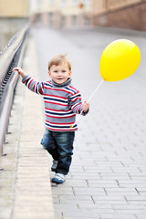 Adorable little boy  with yellow baloon in heand