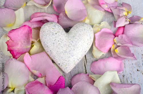 White marple heart with rose petals on wooden background