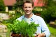 Gartenarbeit im Sommer - Mann mit Kräutern