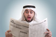 arabian businessman shocked while reading newspaper