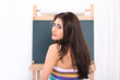 Pretty school teacher looking back from blackboard