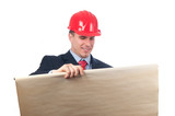 Handsome smiling engineer with red helmet looking at blueprint