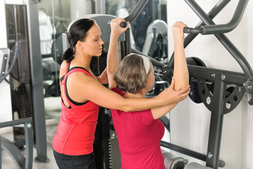 Senior woman at fitness center exercise shoulder