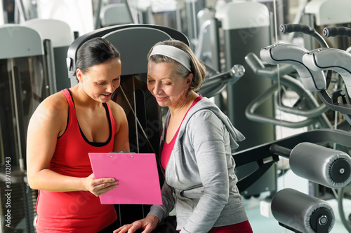 Staande foto Fitness Personal trainer with senior woman at gym
