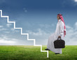 arabian Businessman stepping up the stairs against a green scene