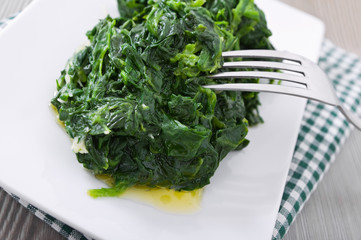 Boiled spinach on white dish. Spinaci bolliti.