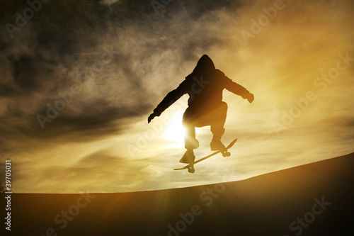 silhouette of skateboarder in sunset