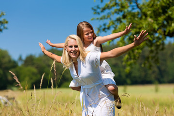 Mutter mit Tochter auf einer Wiese