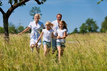 Glückliche Familie läuft in der Wiese