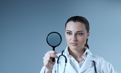 Young female doctor holding magnifying glass in hand