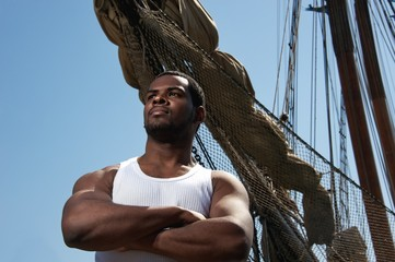 Handsome afro-american sailor against boats.