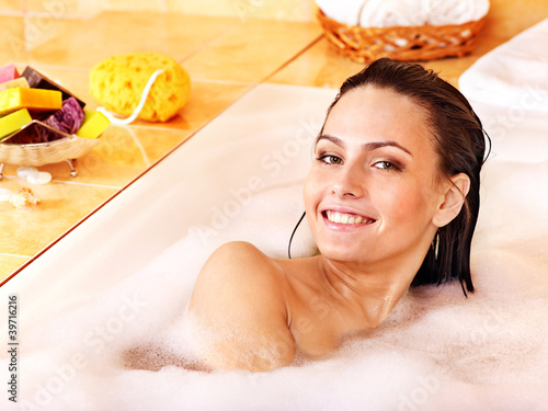 Woman relaxing in bubble bath .