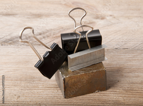 paper clips and a magnet on a wooden background