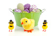 a green bucket with decorated easter eggs with funny easter chic