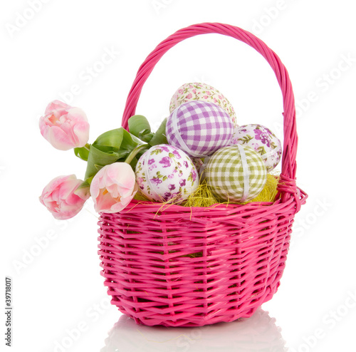 cheerful easter eggs and tulips in a pink wicker basket isolated