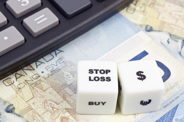 Canadian currency with calculator and dice showing STOP LOSS