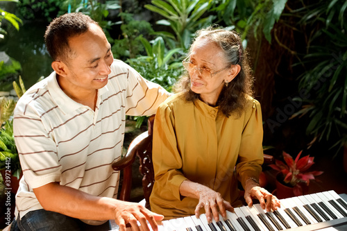 ethnic old mother and son happy playing piano together