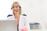 Happy senior business woman with headset working on laptop