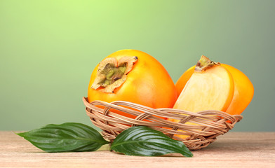 Appetizing persimmons with leaves in pad