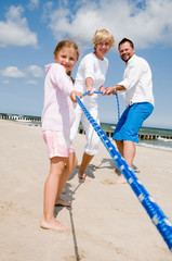 Family playing tug-of-war on sandy beach