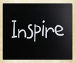 """Inspire"" handwritten with white chalk on a blackboard"