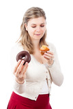 Hungry woman holding sweet muffin and donut