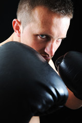Artistic portrait of attractive boxer against black background