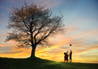 Children playing in sunset with ball, silhouettes