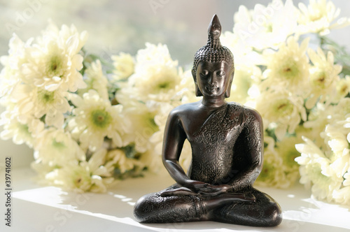 statue of Buddha with white flowers