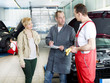 Female customer takes advise by motor mechanics in a garage