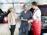 Female customer takes advise by motor mechanics in a garage