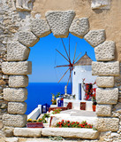Fototapeta Windmill through an old window in Santorini island, Greece