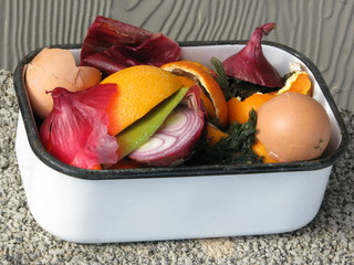 Colorful kitchen compost in a vintage white enamel container.