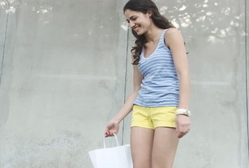 Happy brunette model shopping and laughing slow motion