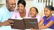 Young Ethnic Family Enjoying Photograph Album
