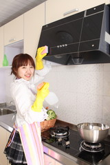 A Chinese woman is cleaning in the kitchen.