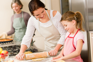 Young girl prepare apple pie with mother