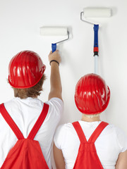 Young worker couple is painting a white wall