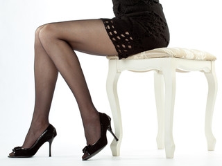 Beautiful legs of young woman sitting on a banquette