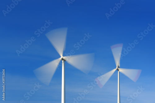 Two wind turbines in movement against blue sky - 39753656