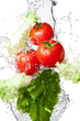 Three Fresh red Tomatoes and lettuce in splash water Isolated on
