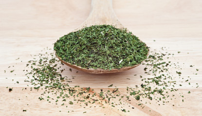 Chopped coriander cilantro leaf on wooden serving spoon with sel