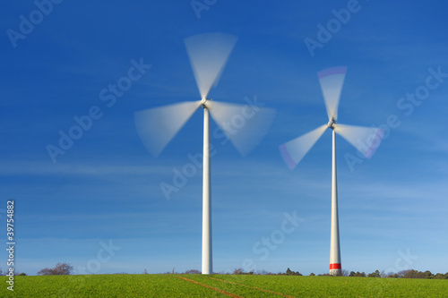 Two wind turbines in movement on a green field - 39754882